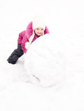 Cute smiling little girl makes snowman in winter day Stock Image