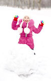 Cute smiling little girl makes snowman in winter day Royalty Free Stock Photo