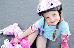 Cute smiling little girl in pink roller skates and protective ge Royalty Free Stock Photos