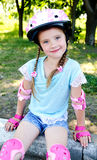 Cute smiling little girl in pink roller skates Stock Photos