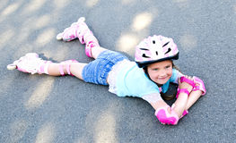 Cute smiling little girl in pink roller skates Stock Photo