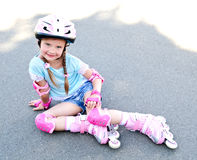 Cute smiling little girl in pink roller skates Stock Image