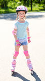 Cute smiling little girl in pink roller skates Royalty Free Stock Photography