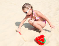 Cute smiling little girl playing on beach Stock Images