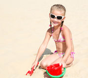 Cute smiling little girl playing on beach Stock Image