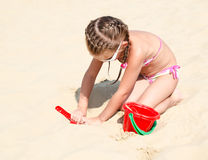Cute smiling little girl playing on beach Royalty Free Stock Image