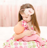 Cute smiling little girl playing with a doll Royalty Free Stock Photos