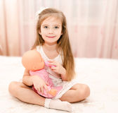 Cute smiling little girl playing with a doll Stock Photography