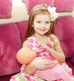 Cute smiling little girl playing with a doll Stock Photos