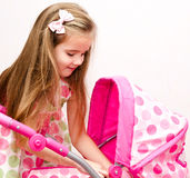 Cute smiling little girl playing with her toy carriage and doll Stock Photography