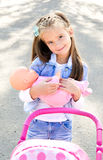 Cute smiling little girl playing with her toy carriage Stock Images