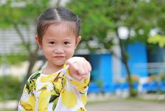Cute smiling little girl pointing at camera in the garden stock photo