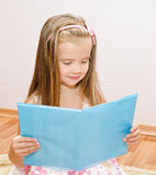 Cute smiling little girl reading a book Royalty Free Stock Photography