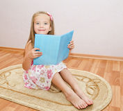 Cute smiling little girl reading a book Royalty Free Stock Photos
