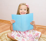 Cute smiling little girl reading a book Stock Photo