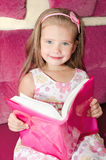 Cute smiling little girl reading a book Stock Photography