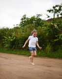 A cute smiling little girl running barefoot in a countryside landscape along a country path Royalty Free Stock Photos