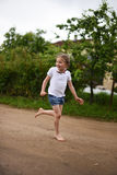 A cute smiling little girl running barefoot in a countryside landscape along a country path Stock Photography