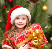 Cute smiling little girl in santa hat with gift box Stock Photo