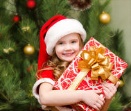 Cute smiling little girl in santa hat with gift box Royalty Free Stock Photo