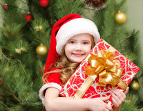 Cute smiling little girl in santa hat with gift box Royalty Free Stock Images