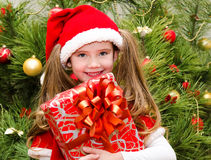 Cute smiling little girl in santa hat with gift box Royalty Free Stock Photography
