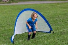 Cute smiling little girl standing in soccer net royalty free stock image