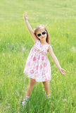 Cute smiling little girl in sunglasses on the meadow Royalty Free Stock Images