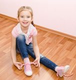 Cute smiling little girl tying her shoes Stock Photography