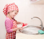 Cute smiling little girl washing the dishes Royalty Free Stock Photo