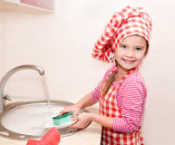Cute smiling little girl washing the dishes Royalty Free Stock Image