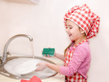 Cute smiling little girl washing the dishes Royalty Free Stock Photography