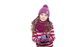 Cute smiling little girl wearing purple knitted scarf, hat and gloves, holding christmas gift isolated on white background. Stock Photo