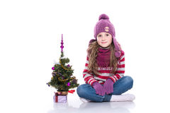 Cute smiling little girl wearing purple knitted scarf and hat, sitting near christmas tree and gift isolated on white background. Royalty Free Stock Photo