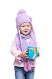 Cute smiling little girl wearing violet knitted scarf and hat, holding christmas gift isolated on white background. Winter clothes Royalty Free Stock Photo