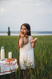Cute smiling little girl in white dress eating bagel with milk in green field, summertime Stock Images