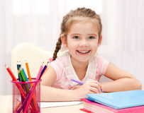Cute smiling little girl is writing at the desk Stock Photos