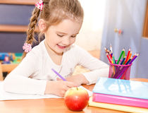Cute smiling little girl is writing at the desk. In preschool Royalty Free Stock Photography