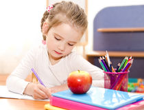 Cute smiling little girl is writing at the desk Stock Images