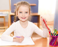 Cute smiling little girl is writing at the desk Royalty Free Stock Photos