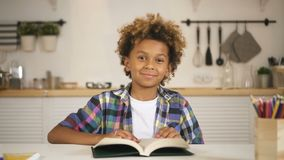 Cute smiling mixed race kid is sitting at table in kitchen and looking straight to the camera. stock footage