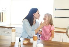 Cute smiling mother and daughter applying face cream stock images