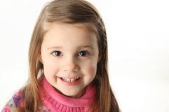 Cute smiling preschool girl. Portrait of a smilng adorable preschool girl wearing a knit pink dress and scarf Royalty Free Stock Image