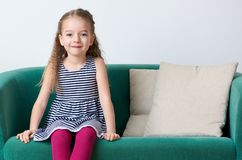 Cute smiling preschooler girl wearing stripy navy blue dress sitting on a couch. Cute smiling preschooler girl wearing stripy navy blue dress sitting on a couch royalty free stock photos