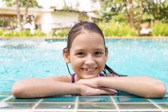 Cute smiling preteen girl at swimming pool edge. Travel, vacation. Childhood concept stock photos