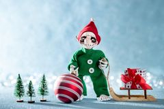Cute Smiling Santas Helper Elf Holding Christmas Bauble and Pulling Christmas Gift on a Sledge. North Pole Christmas Scene.