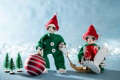 Cute Smiling Santas Helper Elves Holding Christmas Bauble and a Christmas Gift. North Pole Christmas Scene. Elves at work. Cute Smiling Santas Helper Elves stock images