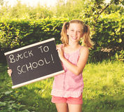 Cute smiling schoolgirl standing with blackboard outdoors. Back
