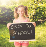Cute smiling schoolgirl standing with blackboard outdoors sunny Stock Images