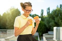 Cute smiling schoolgirl teenager holding a hamburger and orange juice. Back to school outdoor Royalty Free Stock Image